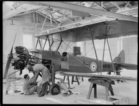 Cadet trainer aircraft A6-15 with two men working on the engine in a warehouse