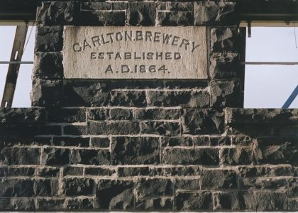 "Exterior wall of a stone building with stone plaque reading "" Carlton Brewery Established A.D 1864"""