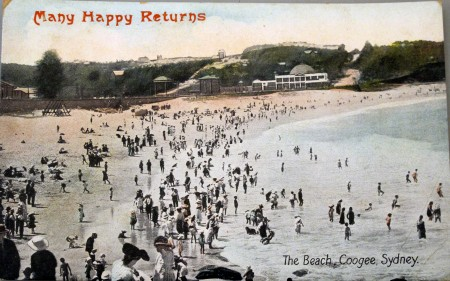 """Image of a busy Coogee beach with the text """"Many Happy returns"""""""