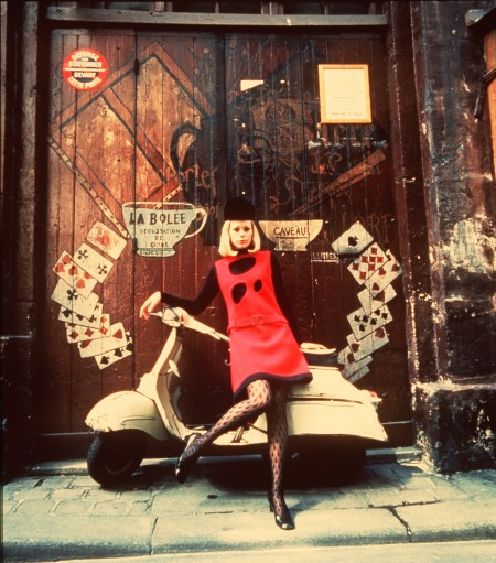 Woman wearing bright red 1960's dress leaning against a white vespa scooter in front of a tall double wooden doors