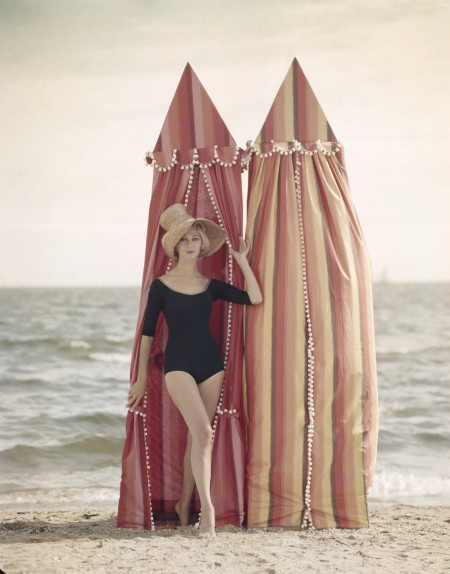 Woman dressed in one piece, love sleeve swimming costume on beach with two tall tents