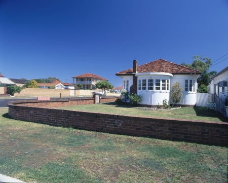 White one story house with large grassy front yard. House at Monterey, Sydney