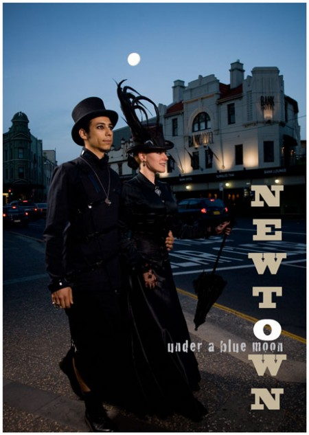 """A man and women in Gothic attire on King Street, Newtown with the Bank Hotel in the in the background. Text in image """"Newtown - Under a blue Moon"""""""