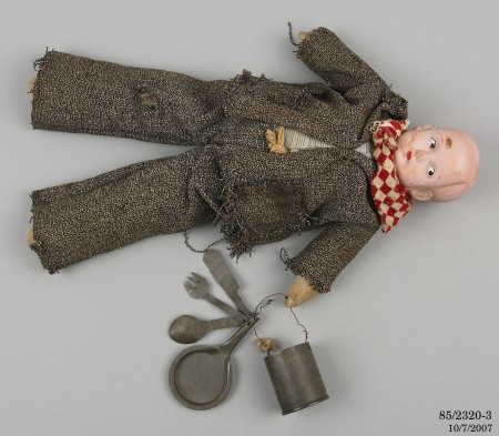 Doll dressed as a swagman, in a lying down position