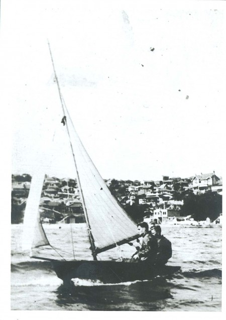 Black and white photo of two men in a sail boat on the water