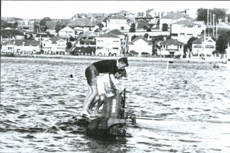 Two men standing and holding on to the keel of their capsized sail boat