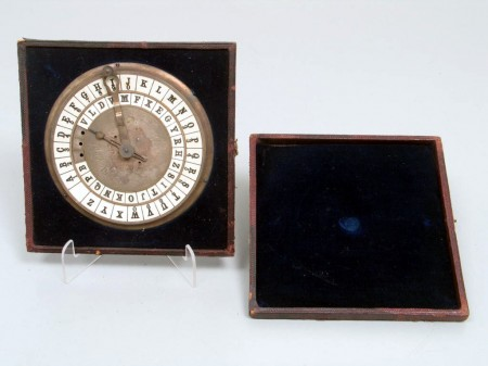 Cryptograph, clock looking piece with two hands and lettering around the circumference