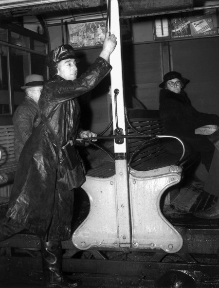Black and white photograph of man in a long coat ringing the bell on a tram