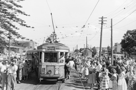 Black and white photo of people watching a tram