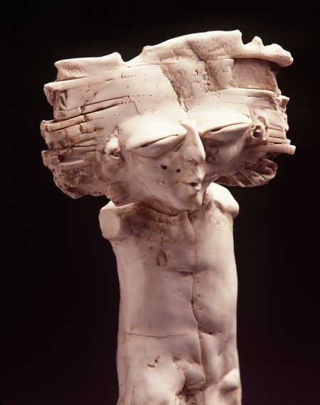 White sculpture of a man with irregular face and big hair