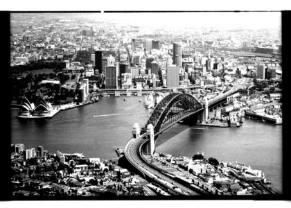 Black and white aerial photograph of Sydney Harbour and city