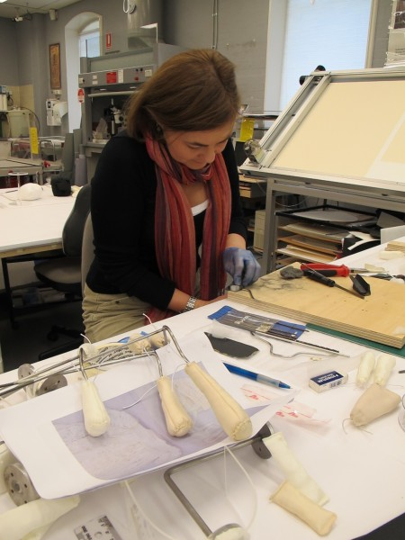 Conservator Rebecca Ellis filing the stainless steel support rods in the Conservation Lab at the Powerhouse museum