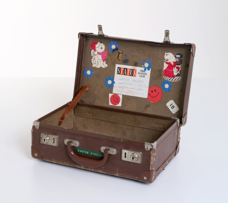 Brown suitcase with childrens stickers stuck on the inside - Status fibre school case made by Consolidated Plastics Industries