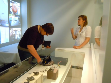 Two women stand beside a showcase filled with museum objects. The woman on the left is placing something inside the showcase.