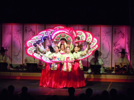 Korean dancers on stage dressed in yellow shirts and pink skirts stand in two concentric circles holding up large intricately decorated fans.