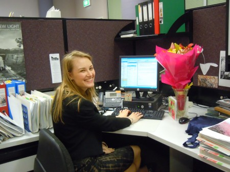 A woman working at a computer at an office desk. She is turning around to smile at the camera. Her desk contains various folders and paperwork as well as a bouquet of bright flowers and a card.