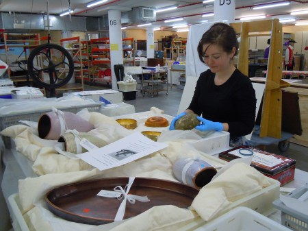 A woman stands at a table covered in plastic trays containing museum artefacts. The woman is wearing blue rubber gloves and handling a ceramic object. She is working in a warehouse environment with crates, trolleys, tables and shelving around her.