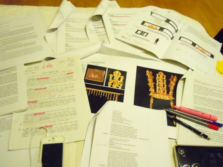 Multiple documents and writing utensils laid out on a desk. One document contains images of several intricate golden artefacts and another contains exhibition design drawings.