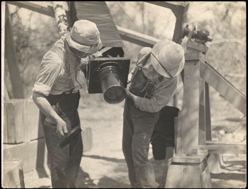 Sepia photograph showing two men adjusting the end of a telescope. The telescope is attached to a large frame set up in bushland. Both men are looking towards the ground. The men are wearing wide brim hats covered with netting.