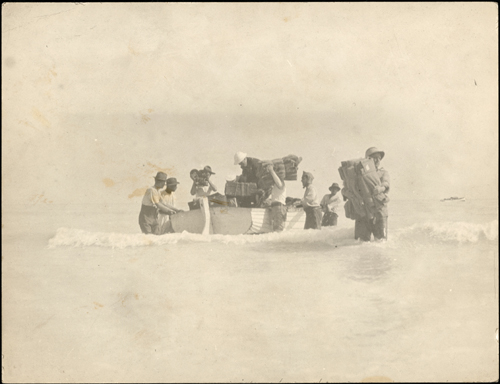 Sepia photograph of a rowboat anchored in shallow water as approximately eight men unload its cargo.