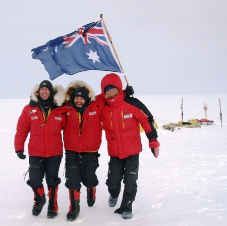 Justin Jones, James Castrission and Aleksander Gamme holding the Australian flag to celebrate the culmination of their expedition