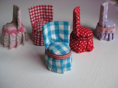 Detail of doll house furniture, five fabric covered chairs