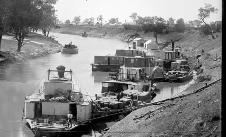 Black and white photograph of multiple paddle steamers docked along a river bank being unloaded.