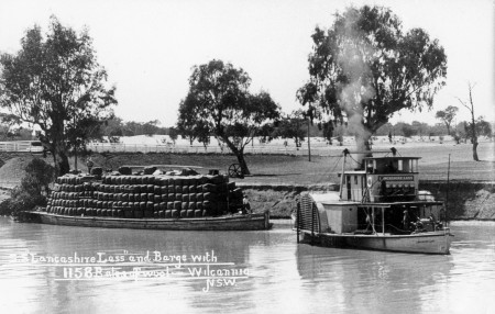 Black and white photograph of a paddle steamer travelling along a river pulling a heavily loaded barge