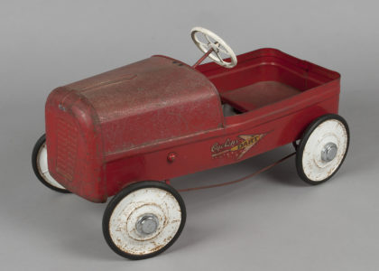 Photograph of red toy pedal car