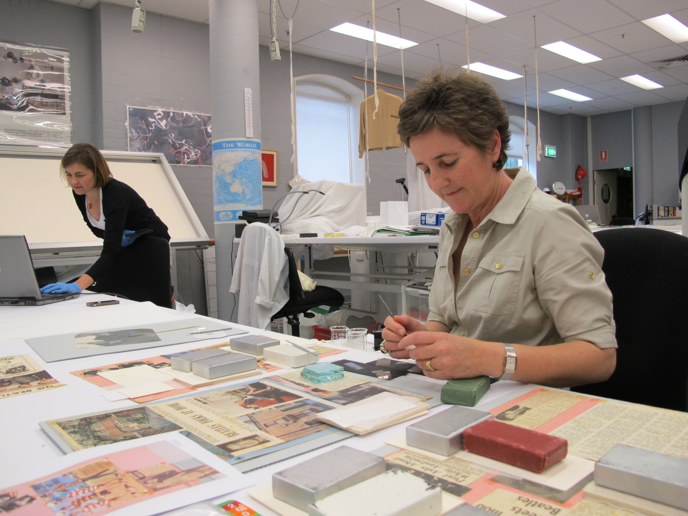 Photograph of conservator re-attaches Beatles clippings