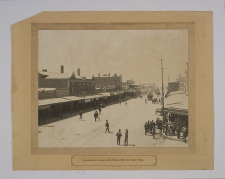 "Photographic print, ""Argent Street Broken Hill"", Silver Gelatine print on paper mounted, Broken Hill, NSW, 1910, Photograph of main street with teams and men standing around. Inscription: ""Argent Street, looking north, Broken Hill New South Wales"