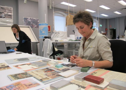 A conservator re-attaches Beatles clippings with Japanese tissue, starch paste and weights.