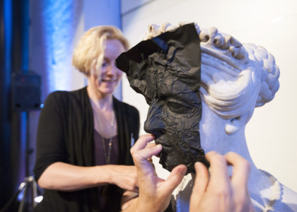 Hadley Howes pictured behind the bust of Queen Victoria, while the hands of Maxwell Stephens are shown applying cine foil to the bust