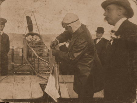 Photograph of Guillaux tying a silk French Tricolour flag to the tail of his Blériot aircraft