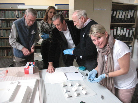 Some of the expedition team and advisors examine the coins at the Museum of Applied Arts and Sciences