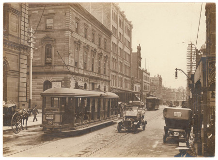 A sepia photograph of a city street lined with sandstone buildings and tram tracks running down the road. Two trams travel away from the viewer on the left track while a car travels towards the viewer on the right side.