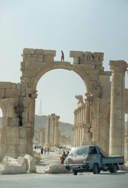 Gate with a dare-devil climber pictured standing on a high arch, Palmyra, 1999, photograph by Paul Donnelly