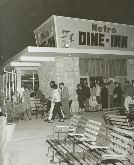 Black and white photograph of men and women lining up to enter a building called the 'Metro Dine-Inn'. The building is surrounded by patio chairs and pot plants.