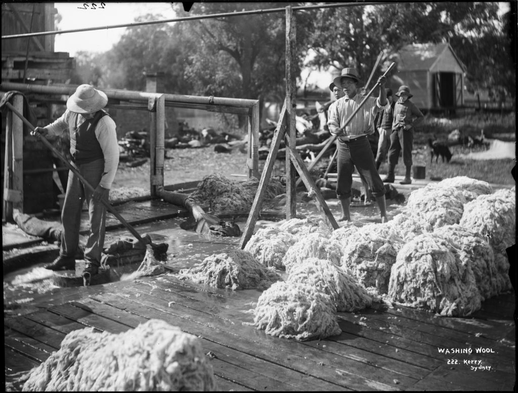 Black and white photograph of three men with pitch forks standing on a deck with mounds of wool beside them. The men are washing the wool in large vats of water in the deck floor, which are fed from a series of pipes. Two men watch on from behind.