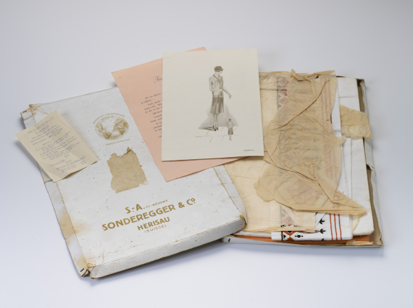 Contents of the Sonderegger & Co dress kit, including box, fabric wrapped in tissue, fashion illustration, washing instructions and list of contents.