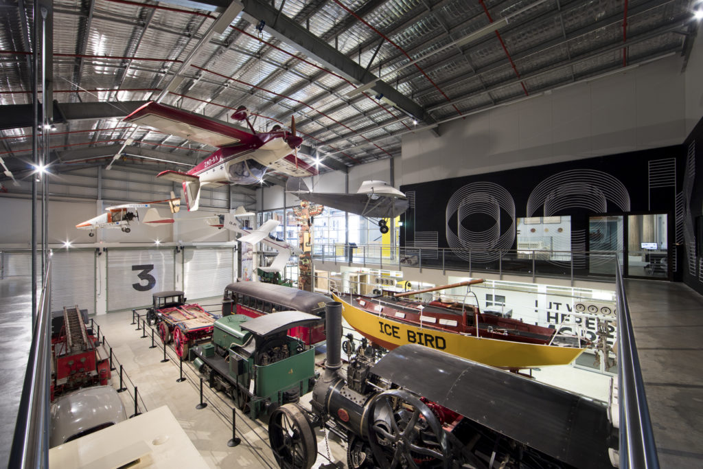 View overlooking a gallery space at the Museums Discovery Centre in Castle Hill. Hanging from the ceiling are several small planes, including one which is upside down. On the level below are other objects from the Museum's transport collection, including a boat, tram carriage, steam train and fire engine.