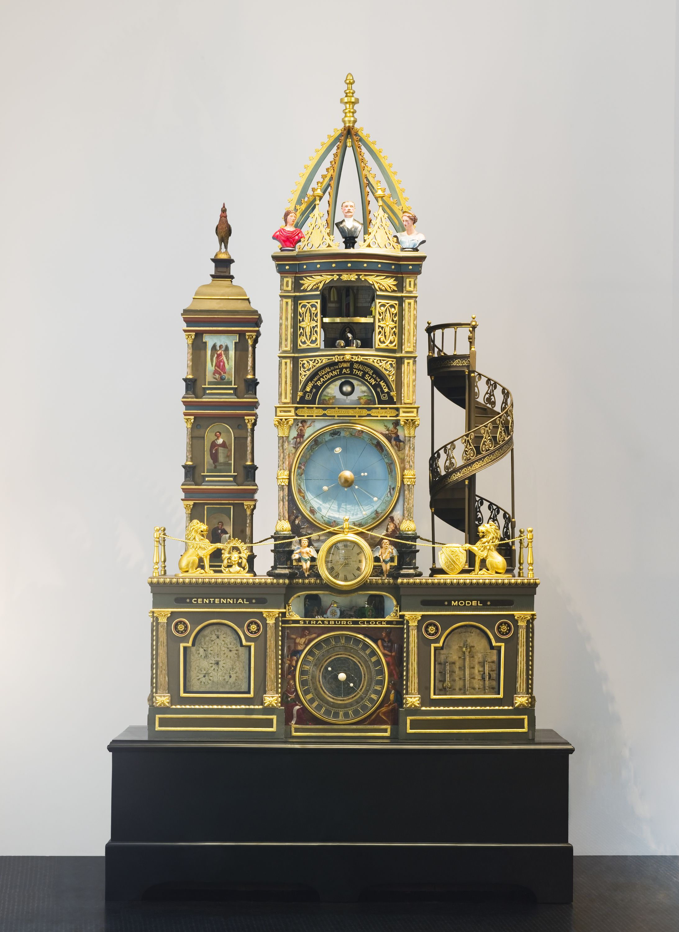 Image of the Strasburg Clock model, featuring a large numbered clock face, golden lions, angelic figures, and planetary bodies.