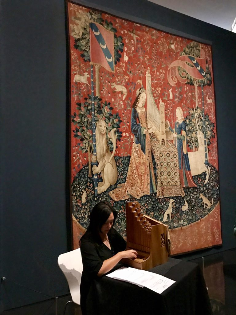 Photograph of musician Grace Chan playing the portative organ, alongside The lady and the unicorn tapestries at the Art Gallery of NSW.