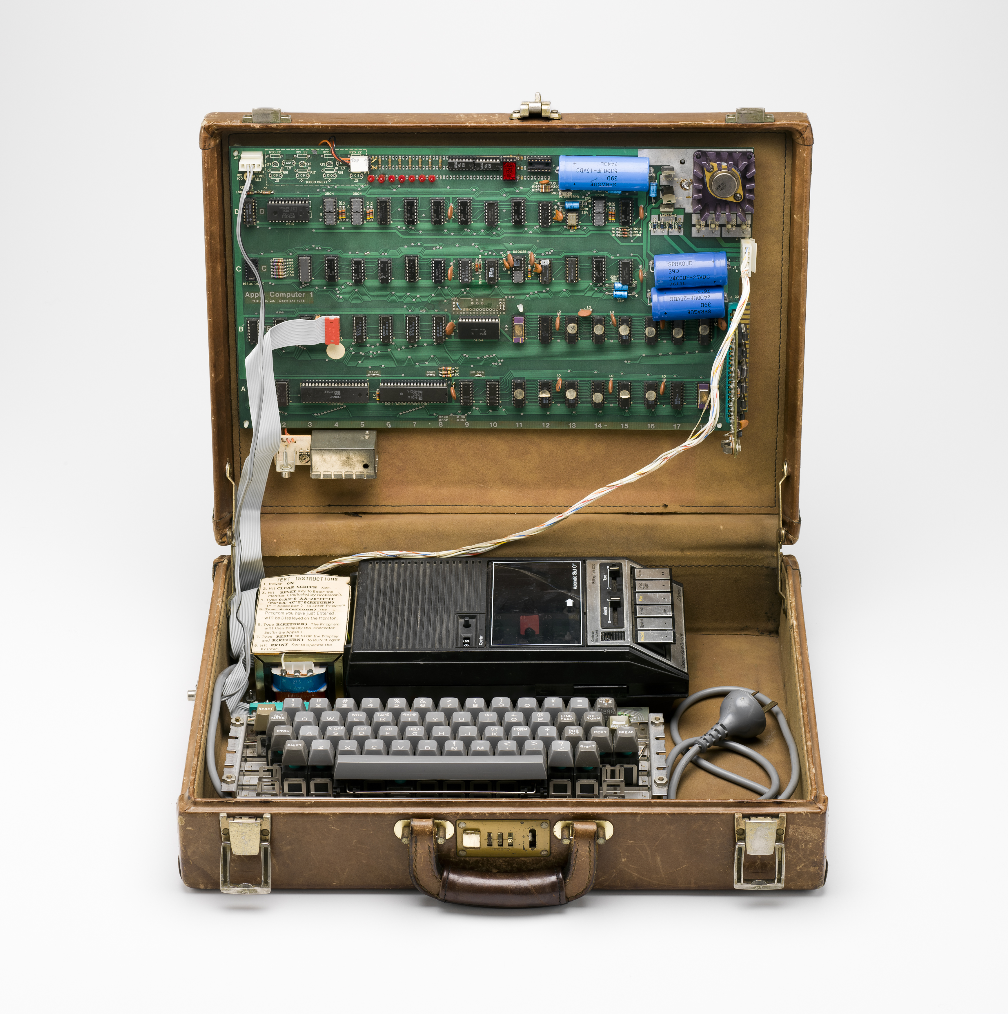 A brown leather suitcase is open withe the green motherboard attached to the inside of the lid. Sitting in the suitcase base is a keyboard and tape recorder.