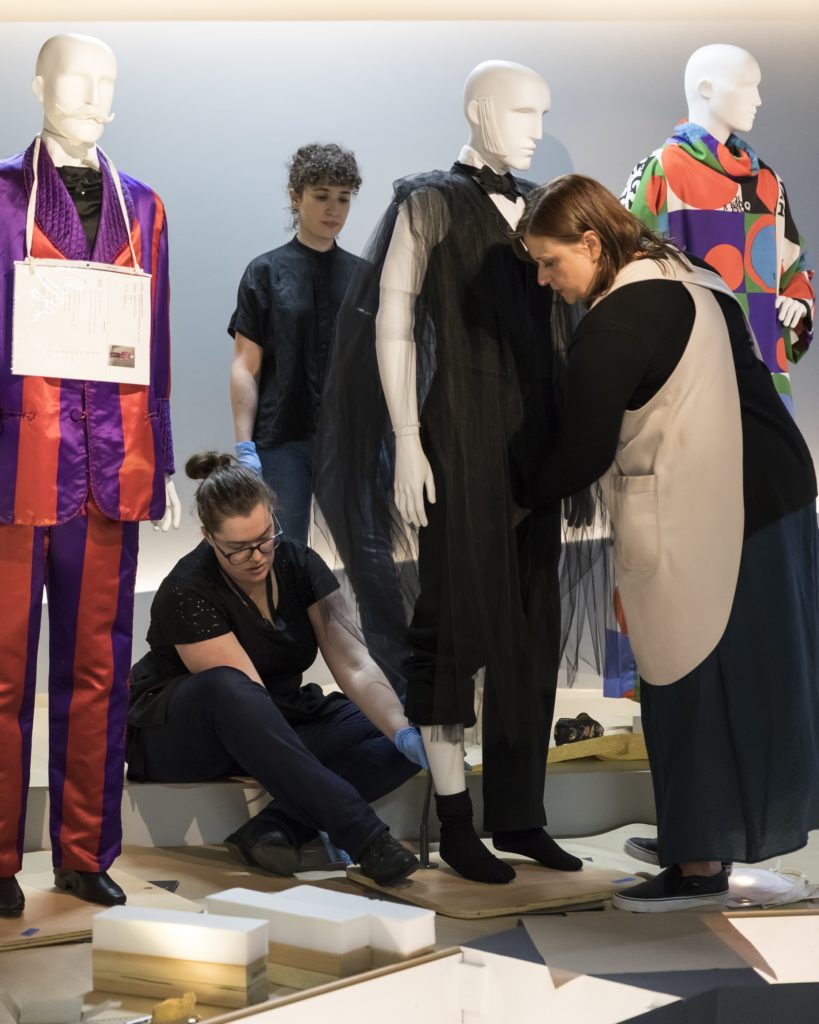 Megan Hall, Conservator (MAAS), Jessica McLean, Registrar (MAAS) and Melinda Kerstein, Costume Installation Specialist (LACMA) securing a half-dressed mannequin to the plinth
