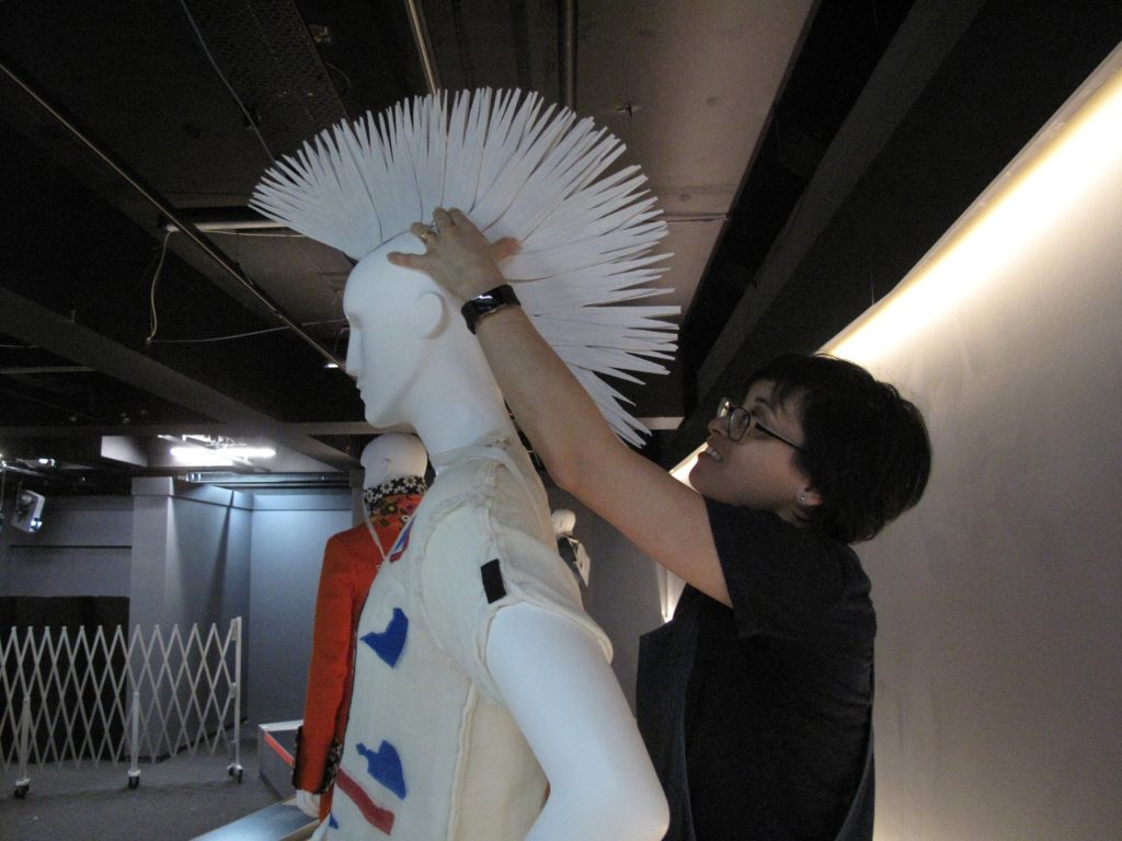 Rachel Tu, Collections Manager (LACMA) placing the wig for Vivienne Westwood and Malcolm McLaren's punk outfit