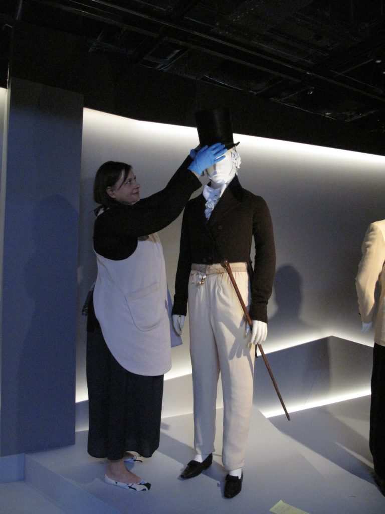 Melinda Kerstein, Costume Installation Specialist (LACMA) adding the silk plush Top hat