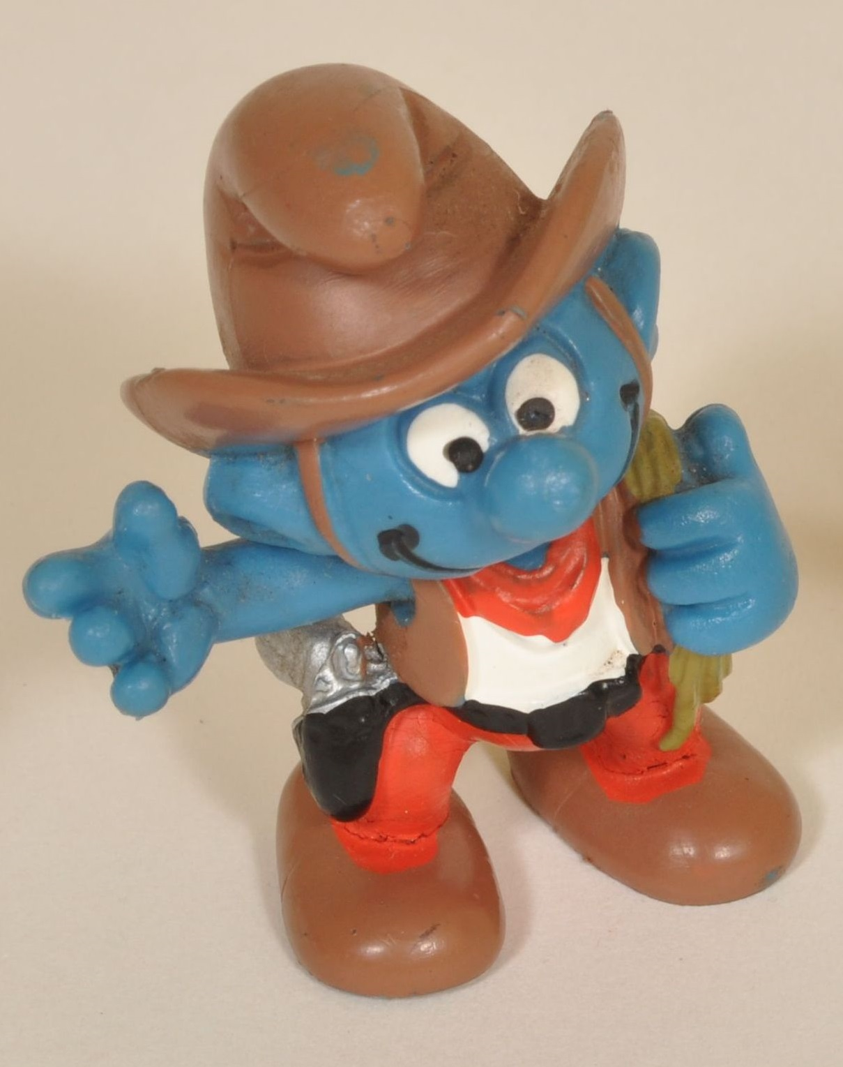 Smurf figurine in cowboy outfit. The figure has a human form with blue skin, googly eyes and a big grin. He is wearing a brown cowboy hat, boots and vest and red scarf and pants. He is holding a rope in one hand and has a gun in a holster on his hip.
