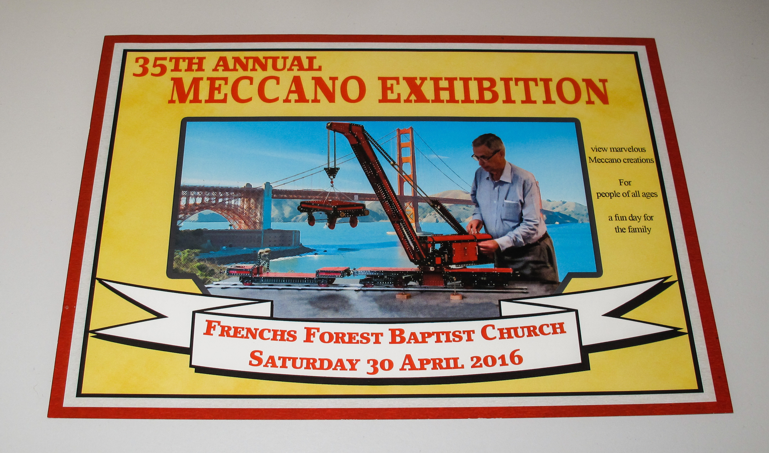 Flyer for the 35th Annual Meccano Exhibition. The flyer has a thick yellow border with the exhibition title at the top and a banner giving the location and date at the bottom (Frenchs Forest Baptist Church, Saturday 30 April, 2016). Inside the border is a photograph of an older man operating a large model crane.
