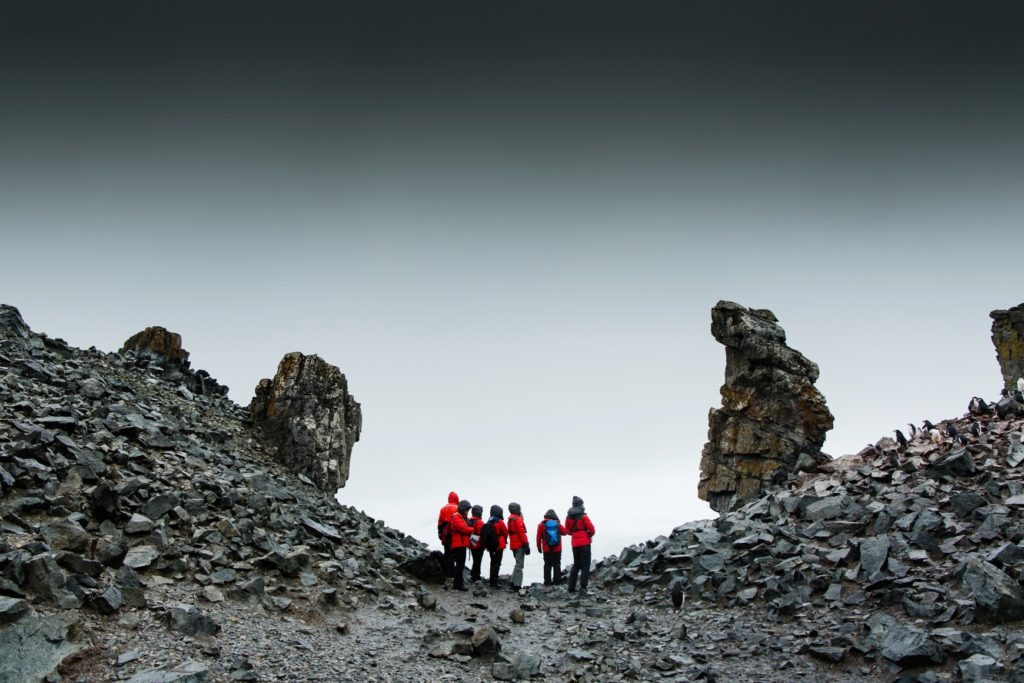 A group of seven people in red jackets stand in the centre of the photo. They are in the middle of two rocky slopes that rise to the left and right. There are some large rock spires standing upright on each slope. The slop to the right has a small colony of penguins. There is a slight pink tinge from their poo on the rocks.